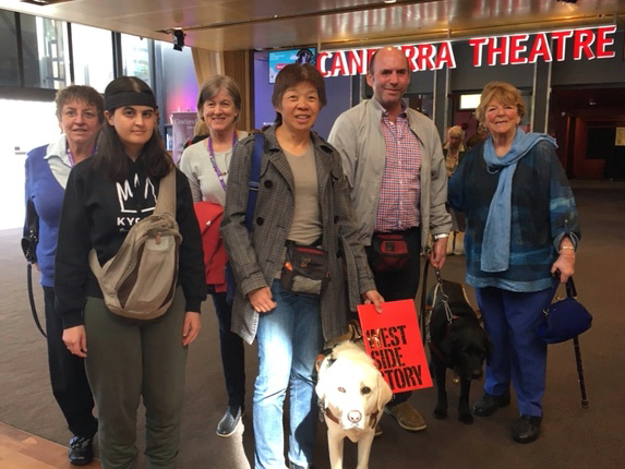Group of three vision impaired people with two guide dogs and three volunteer describers posing in the Canberra Theatre foyer