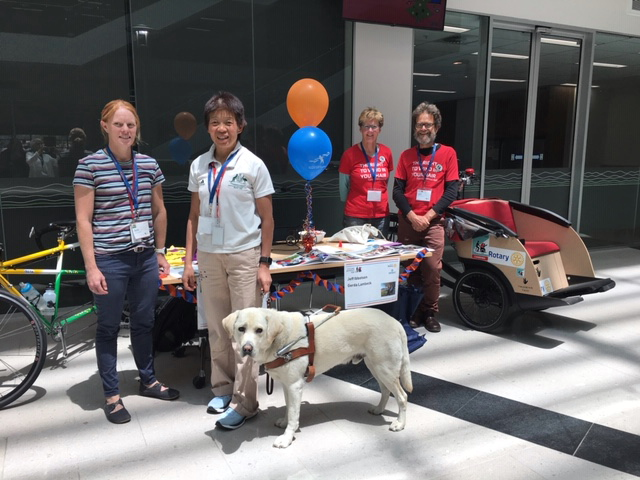 Fitability stand at the Department of Social Services with Beth, Lindy and Comet showing off the tandem bike along with Pedal Power volunteers and their Cycling without Age program rickshaw bike.
