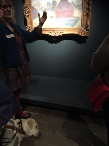 Comet lying flat out at the feet of the curator who is describing one of Monet's haystacks painting in the exhibition