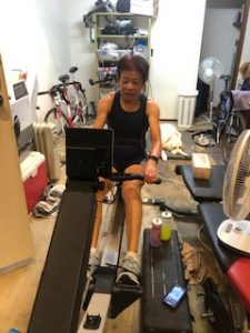 Lindy in action on the Concept 2 indoor rowing machine with Comet snoozing in the background
