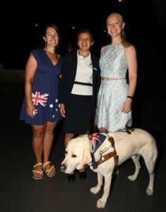 Three ladies standing behind a guide dog in harness