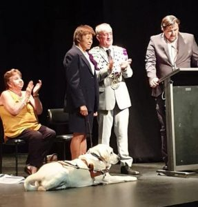 Guide dog in harness lying down on the stage facing the main speaker standing at a lecturn with Lindy and the mayor standing beside each other just behind the dog with a lady seated behind applauding.