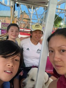 On one of the ferris wheel carriages, seated on one seat is Lindy with a young great niece beside her while on the opposite seat looking around is her niece and young great nephew with me in between
