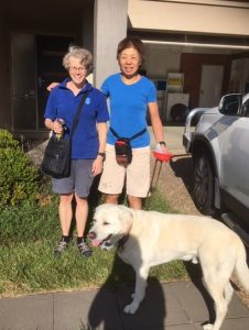 Two ladies standing beside a car in the driveway with an open garage behind and a labrador standing in front of them