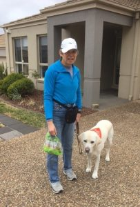 Lindy standing in front of her home carrying a BBQ chicks in one hand and with guide dog Comet wearing a Pawgust bandana on a lead in her other hand